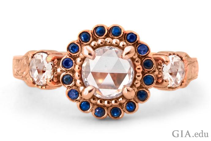 ビクトリア朝時代のデザインを取り入れた、この現代的なリングはローズカットのダイヤモンドをブルーサファイアが囲んでいる。