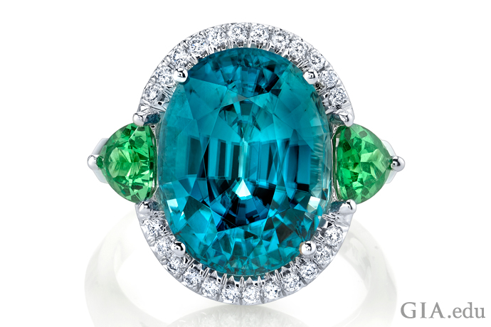 A 6.74 ct cushion cut zircon ring accented with trilliant cut tsavorite garnet side stones and round brilliant cut diamonds set in 18K white gold.