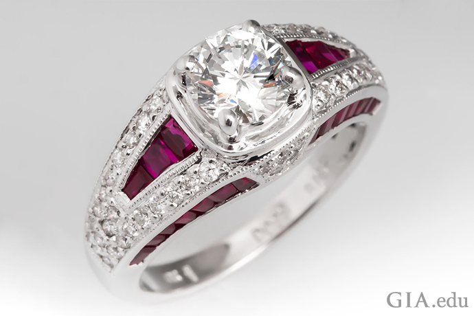 A 1.00 carat round brilliant cut diamond engagement ring surrounded by ruby and diamond accents, set in 18k white gold.