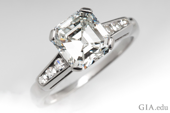 A 2.12 carat emerald cut diamond engagement ring flanked by six round brilliant cut diamonds weighing 0.12 carats.