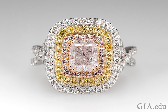 A fancy pink diamond engagement ring encircled by two halos of pink and yellow diamonds set in rose gold and yellow gold.