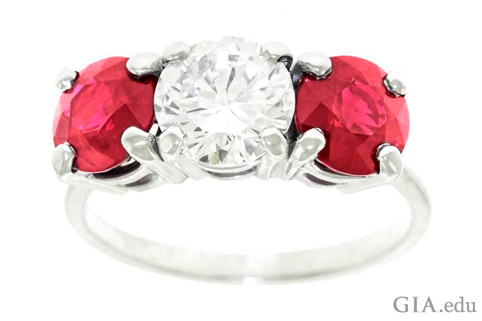 Three-stone gemstone engagement ring featuring two rubies and a round brilliant diamond.