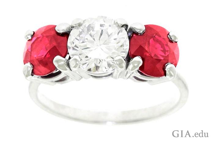 2つのルビーとラウンドブリリアントのダイヤモンドが特徴のスリーストーンの婚約指輪。