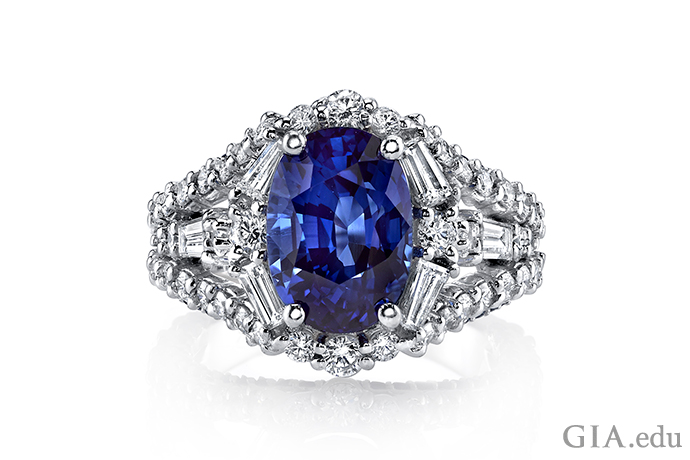 Blue oval sapphire ring with diamonds set in 18K white gold.