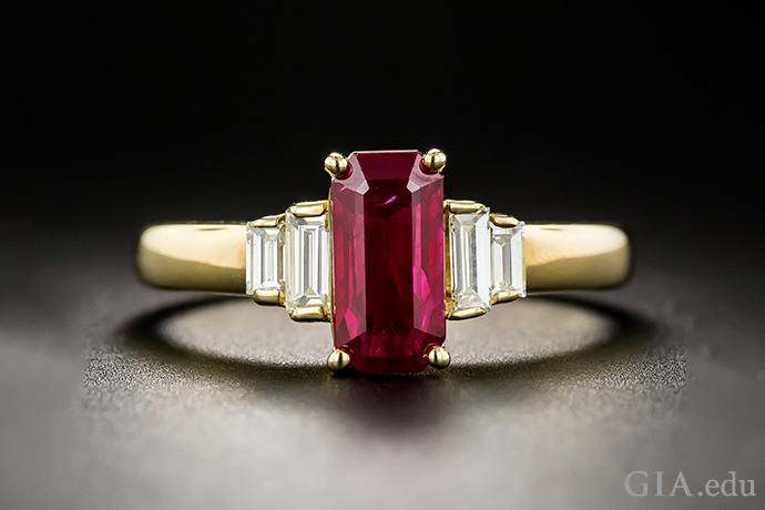 A 1.39 carat elongated emerald-cut Ruby, accented by stepped pairs of bright-white baguette diamonds set in 18K yellow gold.