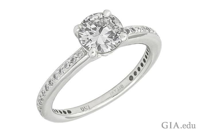 圆形明亮式切工钻石订婚戒指镶嵌在白金戒圈上,篆刻的 750 ppt 字样代表金料的优质程度。