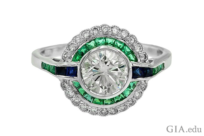 A 1.09 carat round brilliant cut diamond engagement ring from the Art Deco era, featuring emeralds, sapphires set in 18K white gold.