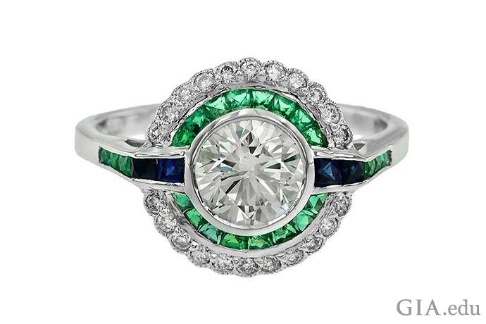 装饰艺术时期的一枚 1.09 克拉圆形明亮式切工钻石订婚戒指,戒指上的祖母绿和蓝宝石镶嵌在 18K 白金中。