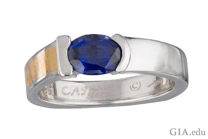 22Kゴールドのインレイがあしらわれたプラチナバンドにブルースピネルがセットされた男性の結婚指輪。