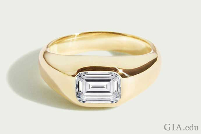 Mens wedding band with an emerald cut diamond center mounted in gold.