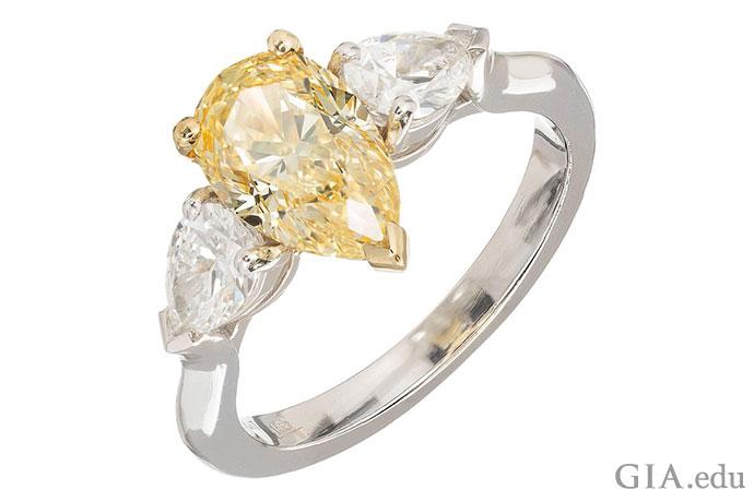这枚订婚戒指的主石是一颗 1.54 克拉浓彩黄色钻石,副石为两颗梨形钻石,镶嵌于铂金镶座之中。