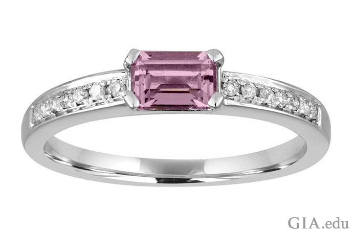 A 14K white gold ring showcasing an amethyst baguette flanked by small diamonds.