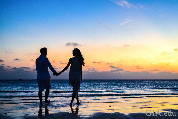 Couple walking on the beach hand-in-hand at sunset.