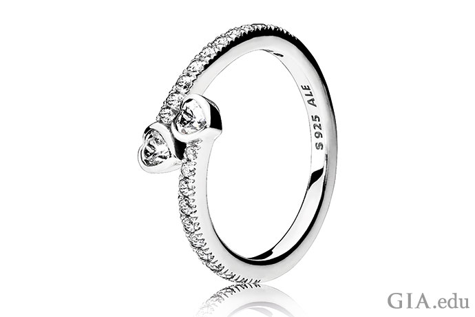 This sterling silver and CZ ring combines the heart motif of claddagh rings with the two-gem motif of toi et moi rings.
