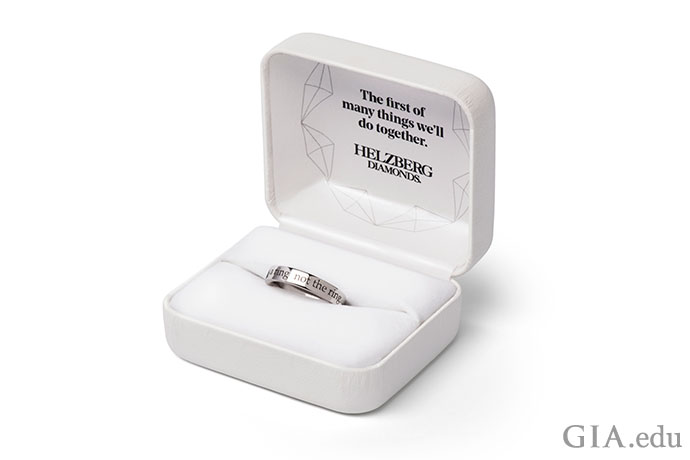 """The Will You? Ring,"" a stainless steel placeholder ring engraved with ""This is a ring, not the ring."""