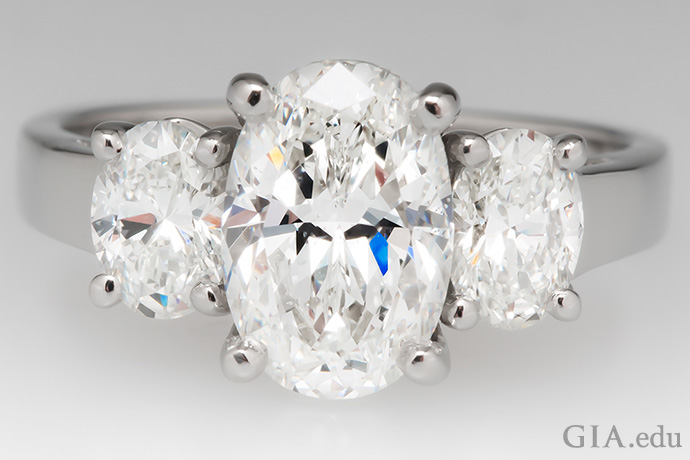 这枚三石订婚戒指镶有三颗椭圆形钻石。1.70 克拉的主石两侧镶嵌着两颗 0.78 克拉的副石。