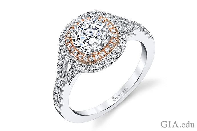 A 1 ct round brilliant cut diamond is surrounded by a double cushion halo of diamonds with two tone accents in white and rose gold. The crown rests on a split shank with a continuous flow of diamonds.