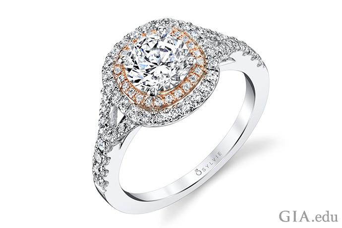 一颗 1 克拉圆形明亮式切工的钻石周围镶嵌着两圈垫型切工的米粒钻,同时以白金和玫瑰金两种色调作为衬托。冠部依托在镶有一圈钻石的分裂戒圈上。