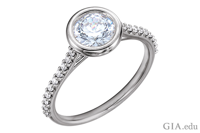 A 14K white gold bezel set semi mount ring featuring a round brilliant cut diamond and diamond melee in the shank.