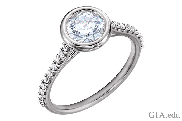 ラウンドブリリアントカットダイヤモンドと、シャンクにダイヤモンドメレーがあしらわれた、14Kホワイトゴールドのベゼルセットのセミマウントリング。