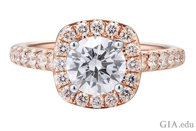 このローズゴールドの婚約指輪のラウンドブリリアントカットダイヤモンドのセンターストーンは、ダイヤモンドのヘイローで囲われており、バンドにはダイヤモンドメレーでアクセントがついている。