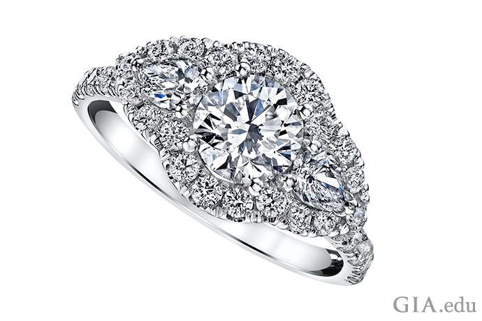 A round brilliant cut diamond halo engagement ring accented by two pear shaped diamonds and melee in the shank.