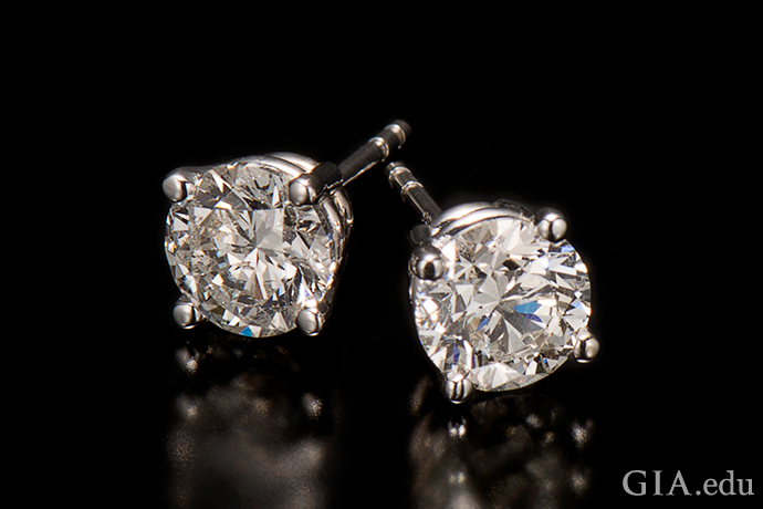A pair of round brilliant cut diamond stud earrings.