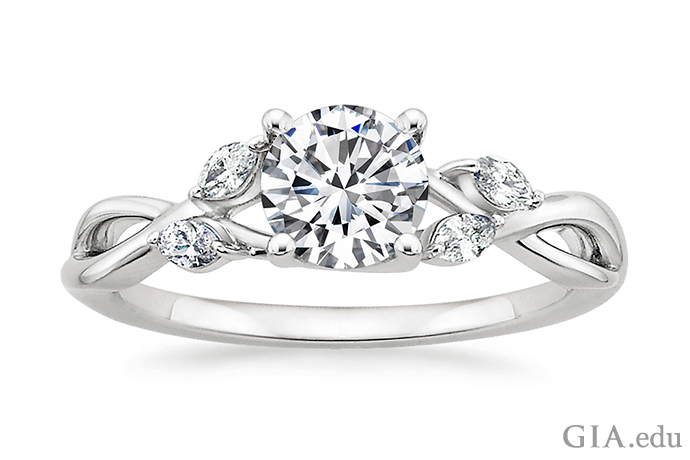 A round brilliant cut diamond engagement featuring wispy vine metal accents and marquise diamond buds.