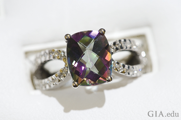 A 3.95 ct Mystic topaz ring, featuring 28 diamond in the shank set in 14K gold.