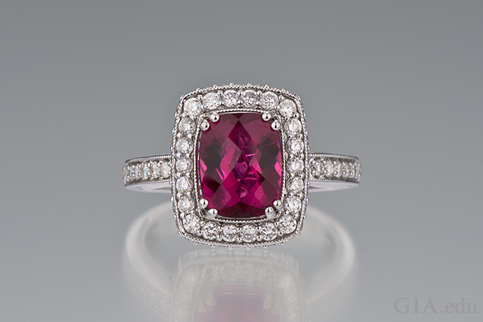 A rubellite tourmaline ring surrounded by diamonds.