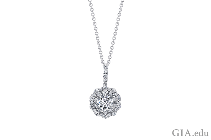 A pendant with a round brilliant center diamond set in 18K white gold.