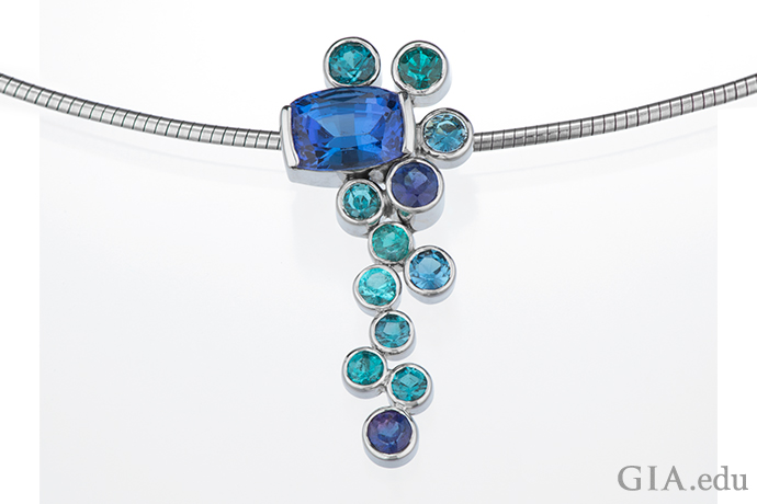 A 14K white gold pendant featuring a cushion cut tanzanite and 12 bezel set Paraíba tourmalines.