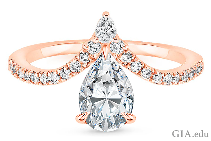 Pear shaped diamond engagement ring set in rose gold with melee diamonds lining a chevron shaped band.