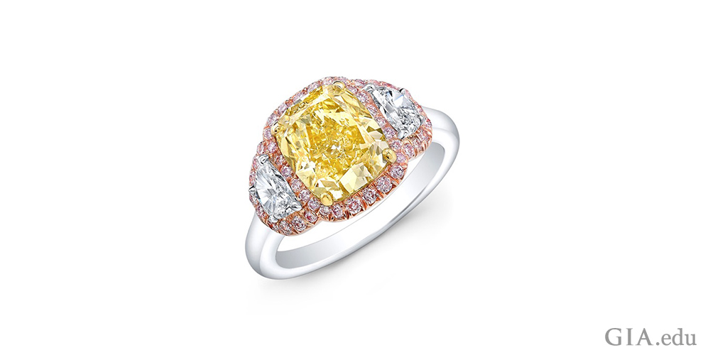 A 3.03 ct fancy yellow cushion cut diamond with 0.54 carats of half-moon cut diamonds set in platinum, yellow gold and rose gold.
