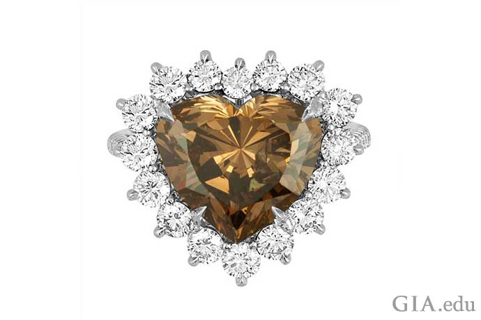 A 7.01 ct heart shaped Fancy Dark yellowish brown diamond and platinum ring accented by 16 round brilliant diamonds.