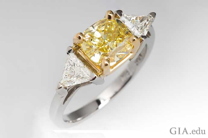 A 2.02 carat Fancy Intense yellow diamond engagement ring flanked by two trilliant cut diamonds.