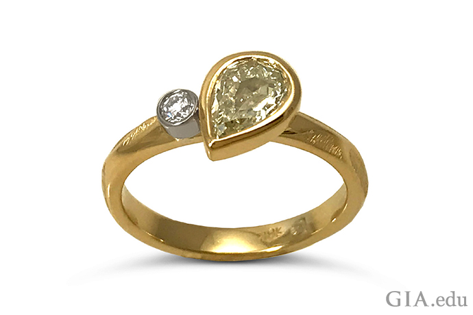 A bezel set 0.58 carat (ct) yellow diamond ring featuring a 0.05 ct colorless diamond.