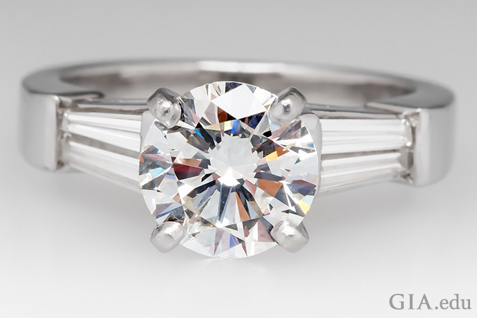 A 1.74 ct round brilliant cut diamond set in platinum and accented by tapered baguettes.