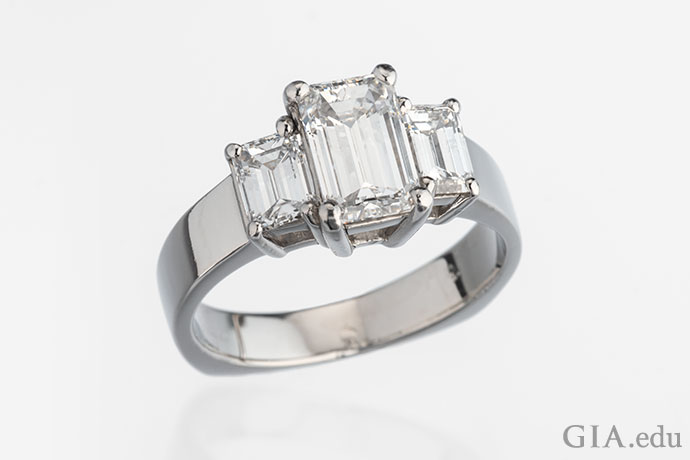 A three-stone emerald cut diamond engagement ring set in platinum.