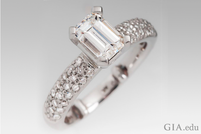 An emerald cut diamond engagement ring with a pave set band.