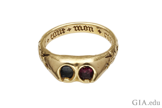 """Posy ring featuring a sapphire and a garnet placed side-by-side. Inscribed with """"oue tout mon coeur,"""" French for """"with all my heart."""""""