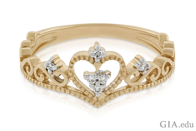 A crown-motif ring set in 14K yellow gold, featuring 0.04 carats of diamonds.