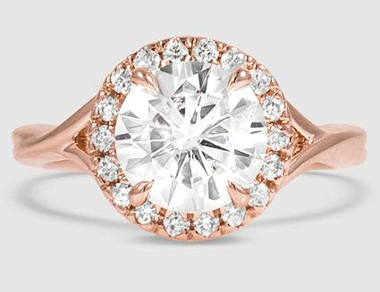 14K rose gold ring is set with a near-colorless round brilliant cut synthetic moissanite.