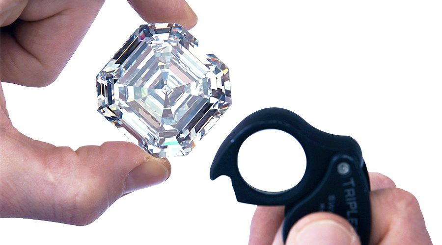 A jeweler examines a step cut, D, VVS1 diamond with a loupe.